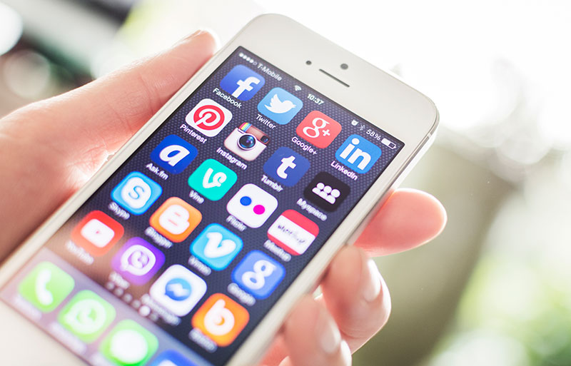 Hand holding a phone showing multiple social media apps on a home screen.